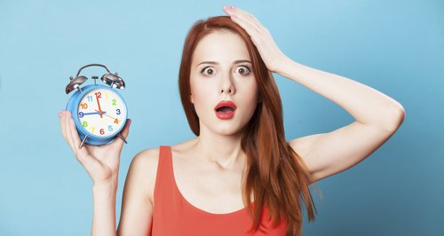 red head holding alarm clock looking shocked
