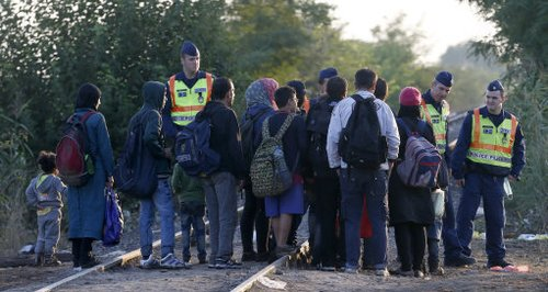 Police stopping Syrian refugees on a railway line