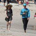 Heather Graham and Chris Martin walking on the bea
